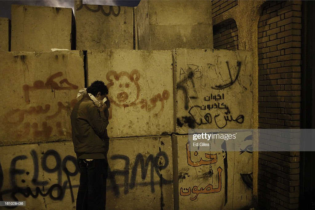 A protester leans against a concrete wall suffering from exposure to tear gas fired by Egyptian riot police during violent protests at the Presidential Palace in Heliopolis on February 8, 2013, in Cairo, Egypt. Protests continued across Egypt against President Morsi and the Muslim Brotherhood two weeks after the second anniversary of the Egyptian Revolution that overthrew former President Hosni Mubarak on January 25, 2011.(Photo by Ed Giles/Getty Images).