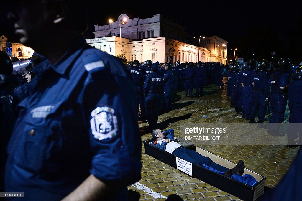 A protester lies in a coffin in front of Bulgarian riot policemen making way for lawmakers and parliament staff leaving the Parliament building during an anti-government protest in Sofia early on July 24, 2013. Bulgarian protesters clashed with police on the 40th evening of massive anti-government rallies in the EU's poorest country after blockading ministers, lawmakers and journalists inside parliament for over five hours. AFP PHOTO / DIMITAR DILKOFF