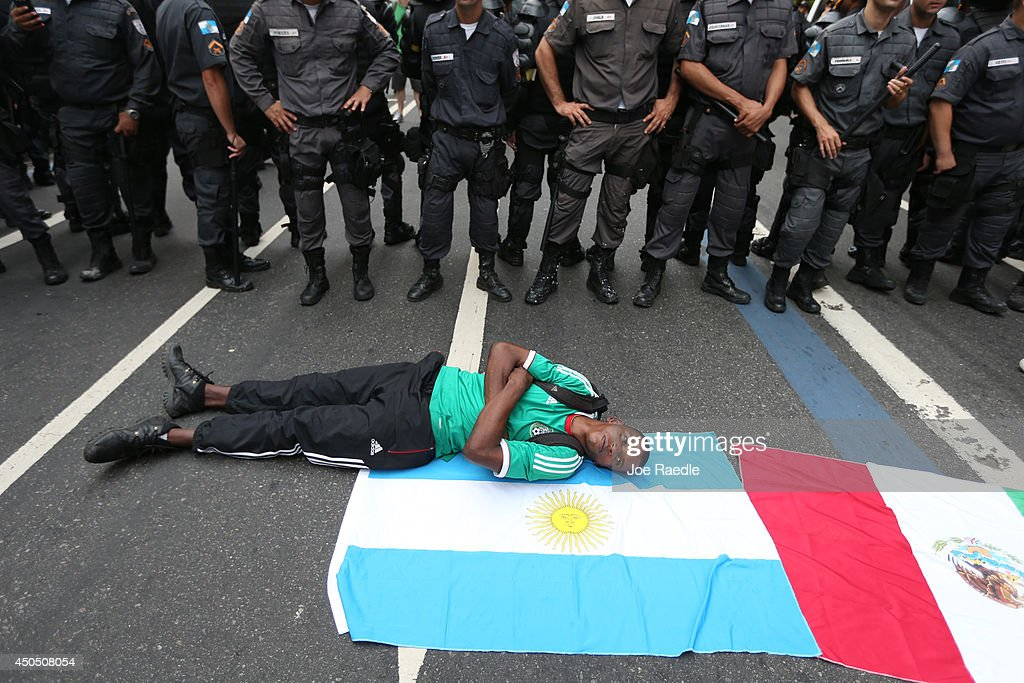 A protester lies on flags in front of police during an anti-World Cup demonstration in the Copacabana section on June 12, 2014 in Rio de Janeiro, Brazil. This is the first day of World Cup play.
