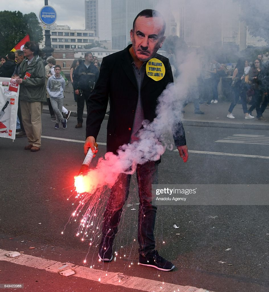 A protester lights a fla during a protest against the new labor law also known as the 'El Khomri law' which has recently proposed by Labor Minister Myriam El Khomri in Paris, France on June 28, 2016. Country-wide protests and strikes, led by uniuons has been continuing for weeks.