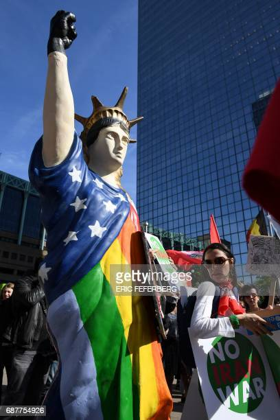 A protester looks at an effigy of the Statue of Liberty wearing a rainbow flag during a demonstration againt the US president in Brussels on May 24...