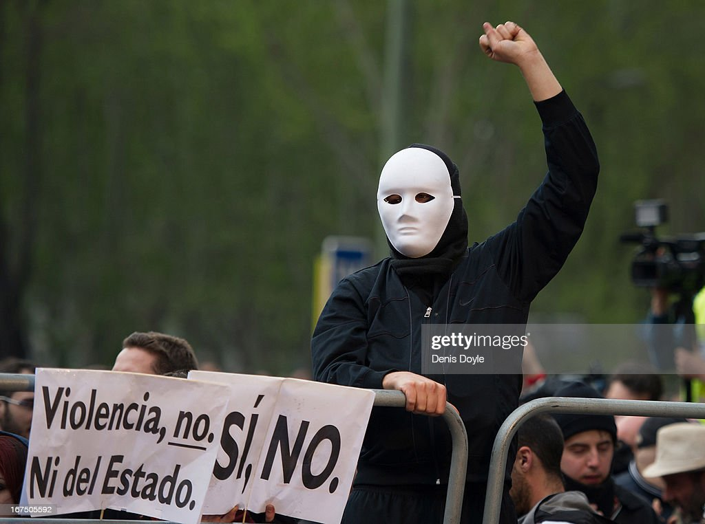 A protester looks at police protecting the Spanish parliament during a demonstration on April 25, 2013 in Madrid, Spain. Demonstrators marched from three locations in central Madrid in an attempt to converge on parliament, demanding a constitutional reform and protesting against financial measures introduced by Spanish Prime Minister Mariano Rajoy.