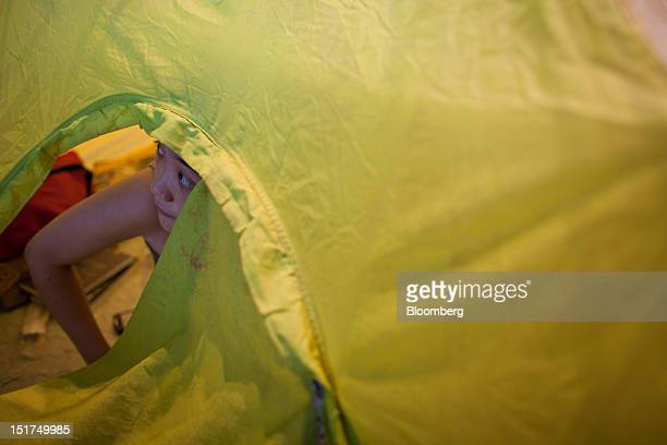 A protester looks out from a tent at the Occupy Central camp in the plaza beneath HSBC Holdings Plc's Asian headquarters in Hong Kong China on...