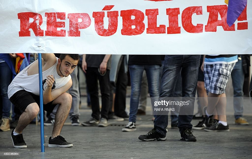 A protester looks under a banner reading 'Republic!' during a demonstration to demand a referendum on the monarchy following the abdication of King Juan Carlos, in the northern Spanish Basque city of Bilbao on June 7, 2014. Dozens of left-wing political parties and citizens organisations came together to demand 'A referendum now!' on the future of the monarchy. Spanish King Juan Carlos' abdication on June 2 revived anti-royalist fervour in the young democracy, sending thousands into the streets clamouring for a referendum on the monarchy itself.