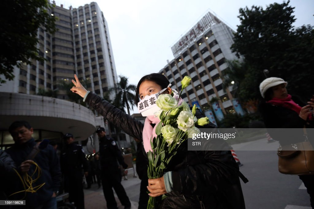 A protester makes a victory sign with her hand while wearing a mask saying 'a barrier for speech' in Chinese, in Guangzhou on January 8, 2013. Protesters rallied for a second day to call for press freedom in China, as social media users and celebrities backed a campaign which poses a test for the nation's new leaders. AFP PHOTO