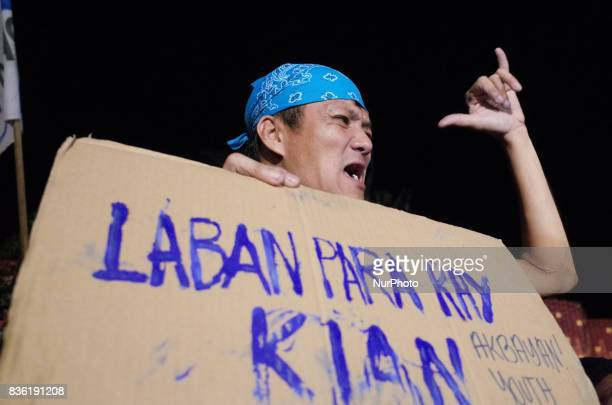 A protester making a letter Y hand gesture shouts slogans during a rally against extrajudicial killings in Quezon City east of Manila Philippines on...