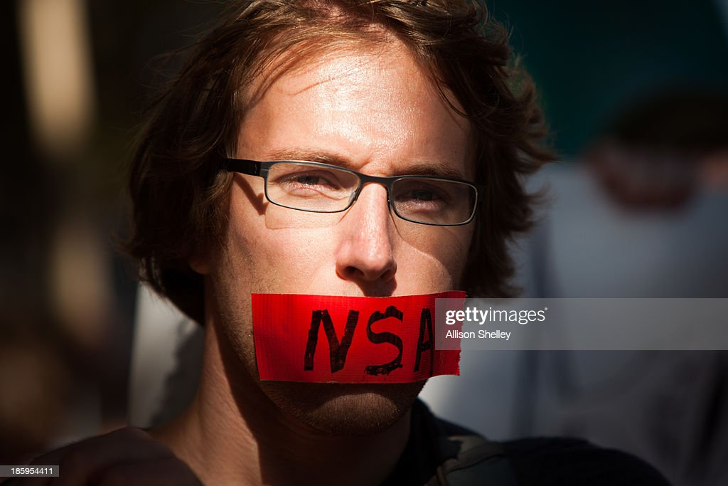 A protester marches with a piece of tape covering his mouth during the Stop Watching Us Rally protesting surveillance by the U.S. National Security Agency, on October 26, 2013, in front of the U.S. Capitol building in Washington, D.C. The rally began at Union Station and included a march that ended in front of the U.S. Capitol building and speakers such as author Naomi Wolf and former senior National Security Agency senior executive Thomas Drake.