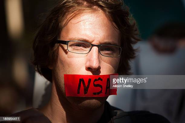 A protester marches with a piece of tape covering his mouth during the Stop Watching Us Rally protesting surveillance by the US National Security...