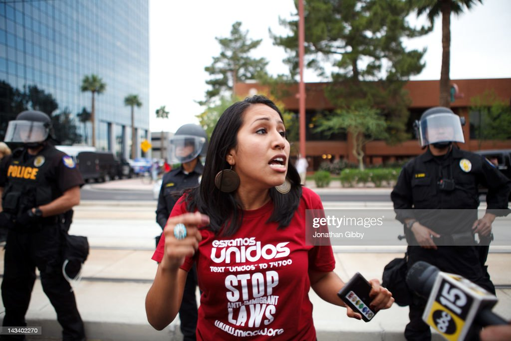 A protester opposed to Arizona's Immigration Law SB 1070 warns others that they will be taken into custody by police officers if they do not disperse April 25, 2012 in Phoenix, Arizona. Immigrant rights advocates held a day of protest in Phoenix, the same day the U.S. Supreme Court heard arguments over Arizona's 2010 immigration enforcement law.
