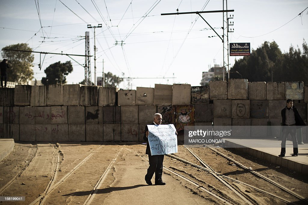 A protester opposed to Egypt's Islamist president holds up a placard in front of a barricade erected by the Egyptian army to protect the Presidential palace in Cairo on December 11, 2012 as demonstrators started to gather in the Egyptian capital for rival rallies for and against a divisive constitutional referendum proposed by President Mohamed Morsi.