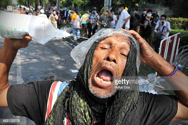 A protester overcome by tear gas pours saliene in his eyes during an antigovernment protest near Government House on December 2 2013 in Bangkok...