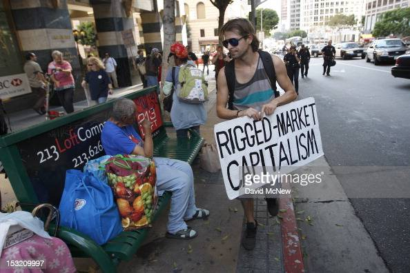 A protester passes a man sitting on a bench during a march in the downtown financial district to mark the oneyear anniversary of the Occupy movement...