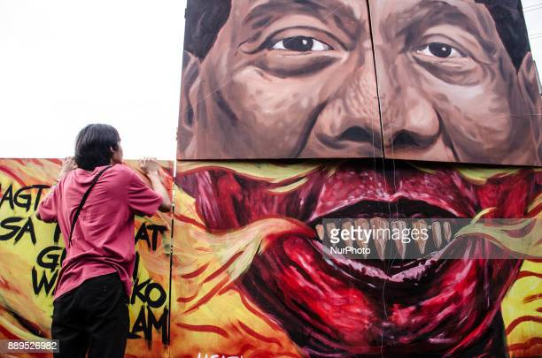 A protester peeks over the effigy that depicts President Rodrigo Duterte as a demon at Bonifacio Shrine in Manila on 10 December 2017 to show their...