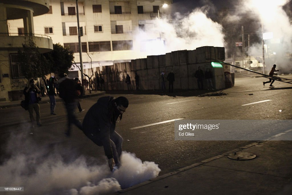 A protester picks up a live tear gas canister fired by Egyptian riot police during violent protests at the Presidential Palace in Heliopolis on February 8, 2013, in Cairo, Egypt. Protests continued across Egypt against President Morsi and the Muslim Brotherhood two weeks after the second anniversary of the Egyptian Revolution that overthrew former President Hosni Mubarak on January 25, 2011.(Photo by Ed Giles/Getty Images).
