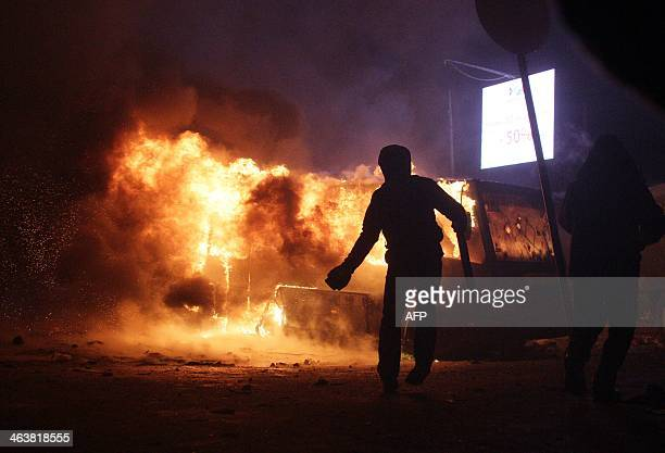 A protester prepares to throw a brick next to a bus in flames as protesters clash with riot police on January 19 2014 during an opposition rally in...