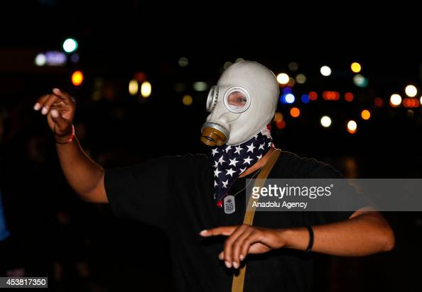 A protester protects himself from the tear gas during a demonstration on August 18 2014 for Michael Brown who was killed by a police officer on...