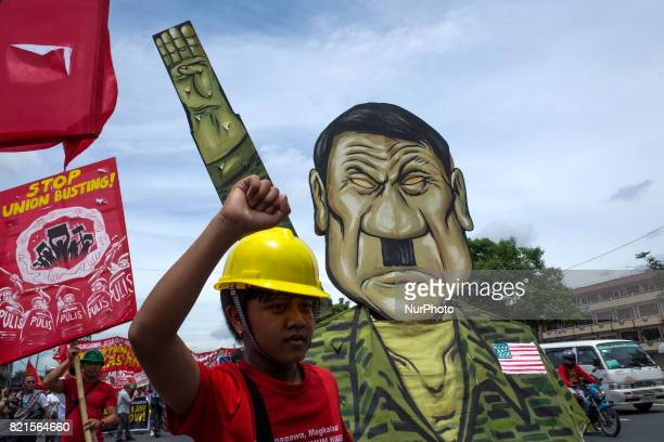 A protester pulls a caricature of President Rodrigo Duterte during a rally coinciding President Rodrigo Duterte's annual State of the Nation Address...