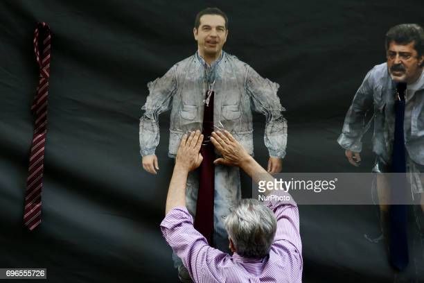 A protester puts a tie on a depiction of Alexis Tsipras at the entrance of the Finance Minisstry mocking the Prime Minister's statement that he will...