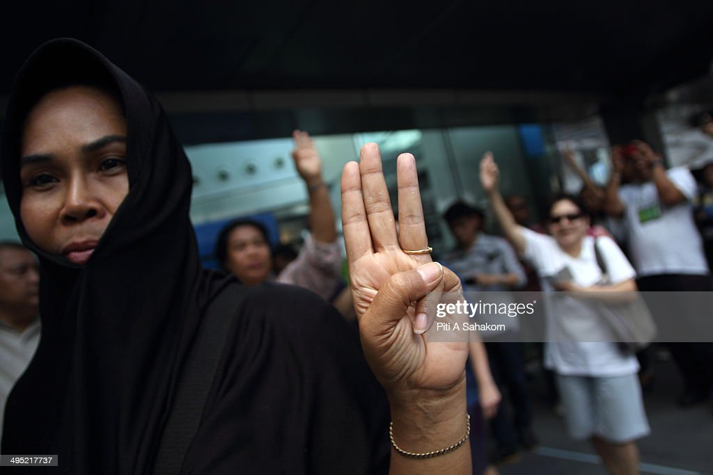 Protester raise three fingers representing liberty, brotherhood and equality during an anti-coup demonstration at a shopping district in Bangkok. Hundreds of demonstrators gathered Sunday near a major shopping mall in downtown Bangkok to denounce the country's May 22 coup despite a lockdown by soldiers of some of the city's major intersections. Troops and riot police were stationed in the central shopping district where one political activist had vowed to host a coup party.