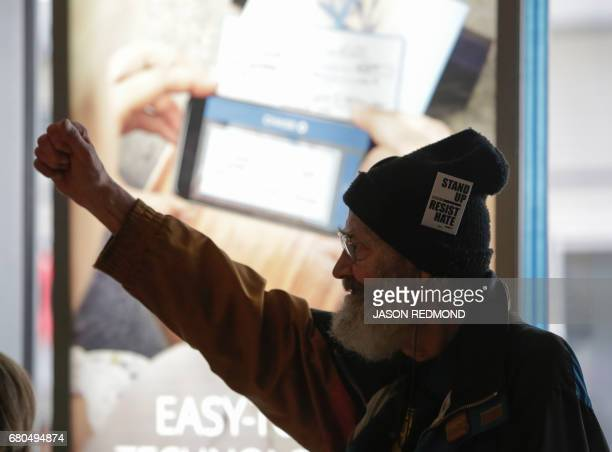 A protester raises a fist as indigenous leaders and climate activists disrupt business at a Chase Bank branch to protest funding tar sands...