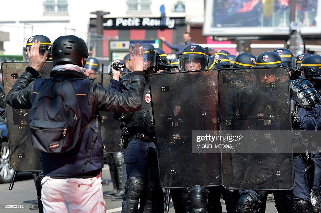 A protester raises his hands as he faces riot police at a traditional May Day demonstration on May 1, 2016, in Paris.