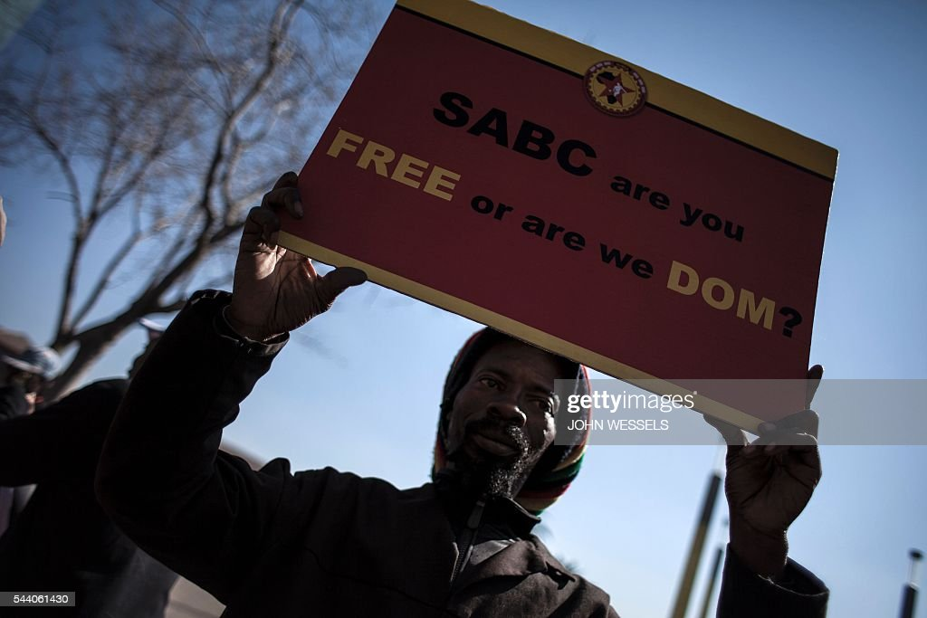 A Protester rallies with others outside the Constitutional Court on July 1, 2016 in Johannesburg to protest against alleged bias and self-censorship in news coverage by the South African Broadcasting Corporation (SABC) ahead of key municipal elections. The South African Broadcasting Corporation (SABC), which is the primary news source for millions of people, has been accused of banning footage of violent protests, blocking opposition campaign adverts and avoiding criticism of President Jacob Zuma. / AFP / JOHN