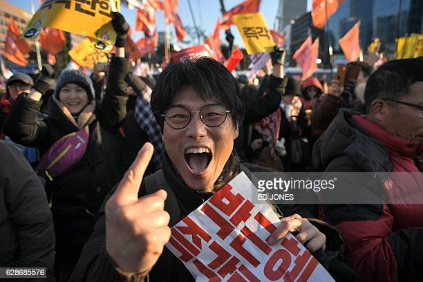 TOPSHOT A protester reacts after the South Korean parliament's successful impeachment of President Park GeunHye as crowds gather outside the National...