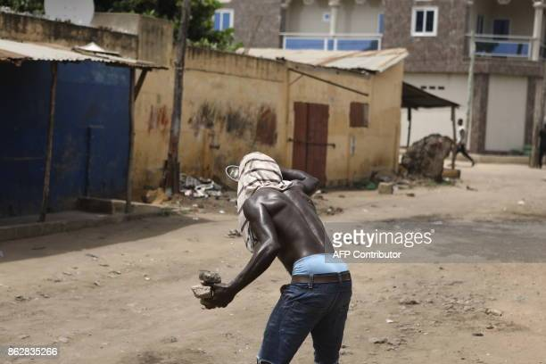 A protester reacts in a street where opposition supporters have erected makeshift barricades and block roads in Lome on October 18 2017 Protesters...