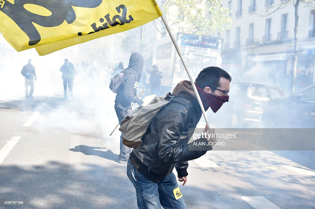 A protester reacts to smoke during a clash with French anti riot police during the traditional May Day demonstration in Paris on May 1, 2016.