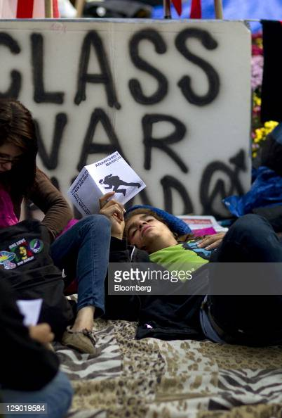 A protester reads a pamphlet during the Occupy Wall Street demonstration at Zuccotti Park in New York US on Monday Oct 10 2011 With the help of...