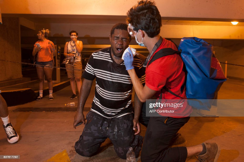 A protester receives aid after police used tear gas to break up protesters gathered outside of the Phoenix, Arizona, Convention Center where US President Donald Trump spoke at a 'Make America Great Again' rally on August 22, 2017. / AFP PHOTO / Laura Segall