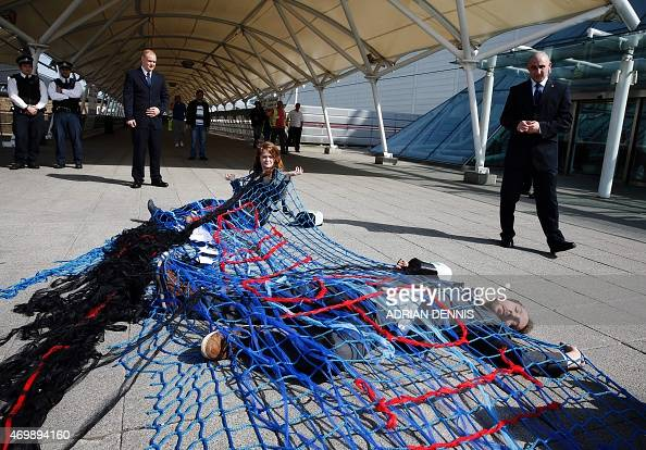 A protester representing UK Tar Sands Network and CoResist stands in a fishing net as shareholders arrive for the BP Annual General Meeting at the...