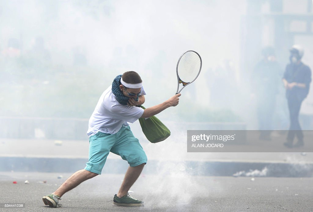 A protester returns tear gas with a tennis racket, during a protest against the government's labour market reforms in Paris, on May 26, 2016. The French government's labour market proposals, which are designed to make it easier for companies to hire and fire, have sparked a series of nationwide protests and strikes over the past three months. / AFP / ALAIN