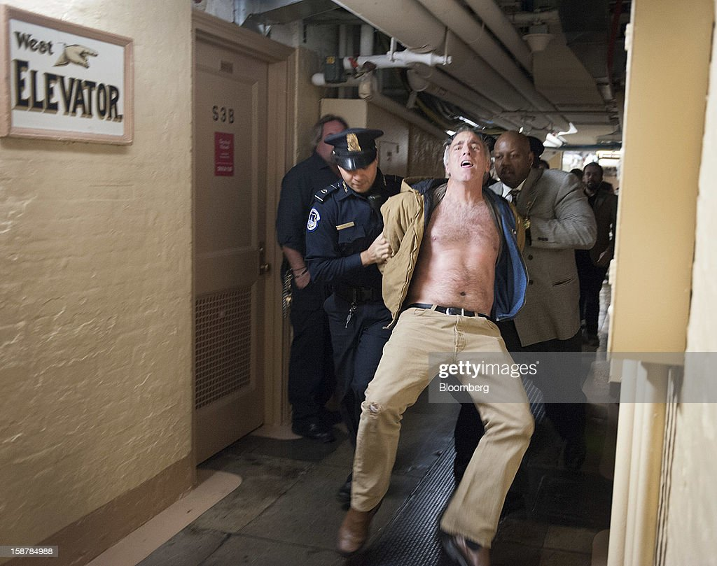 Protester Rives Grogan, who disrupted the U.S. Senate by shouting from the spectator's gallery, is removed from the Capitol building by police through a hallway in the basement in Washington, D.C., U.S., on Friday, Dec. 28, 2012. Rives, an anti-abortion protester, was also removed from the U.S. Senate after a similar incident in June. Photographer: Jay Mallin/Bloomberg via Getty Images