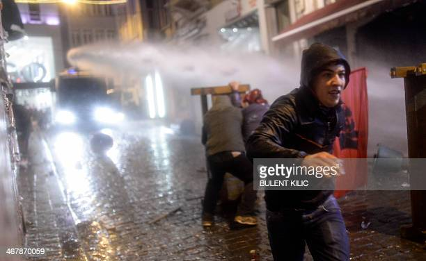 A protester run away from an antiriot police truck firing its water cannon as two other men use a wooden barrier to shield themselves during a...