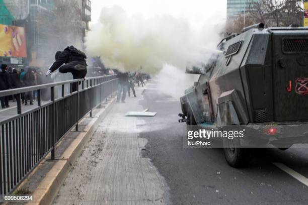 A protester runs away from tear gas thrown from an riot police vehicle Led by the Confederation of Chilean Students the march for universal education...