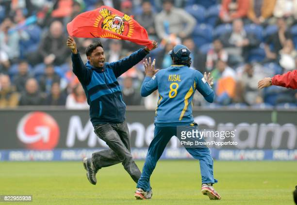 A protester runs on to the field towards Sri Lanka's Kusal Perera during the ICC Champions Trophy Semi Final between India and Sri Lanka at the...