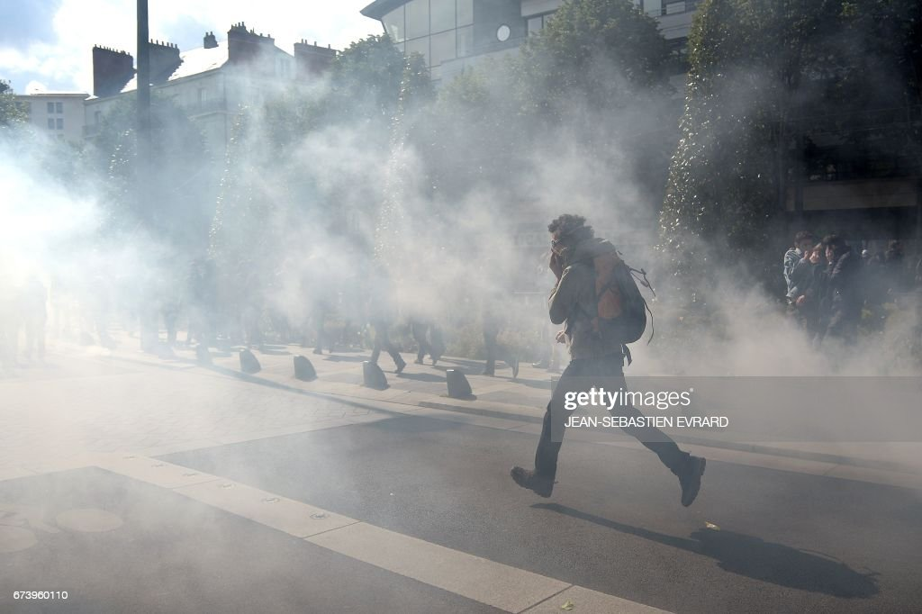A protester runs through a cloud of tear gas during a demonstration against the results of the first round of the French presidential election in Nantes, western France, on April 27, 2017. Youths gathered to protest against far-right leader Marine Le Pen and former banker Emmanuel Macron, who both qualified on April 23 for the May 7 run-off in France's two-stage presidential election.