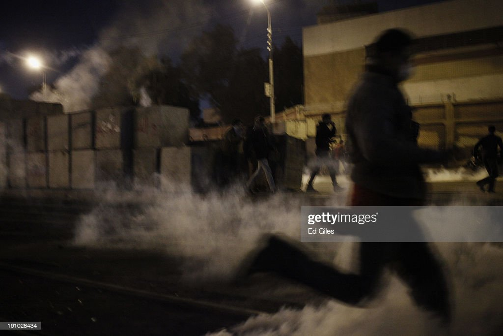 A protester runs through a cloud of tear gas fired by Egyptian riot police during violent protests at the Presidential Palace in Heliopolis on February 8, 2013, in Cairo, Egypt. Protests continued across Egypt against President Morsi and the Muslim Brotherhood two weeks after the second anniversary of the Egyptian Revolution that overthrew former President Hosni Mubarak on January 25, 2011.(Photo by Ed Giles/Getty Images).