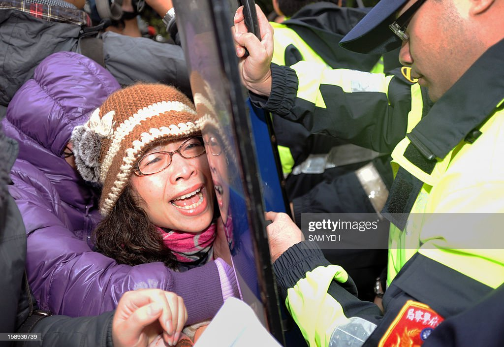 A protester scuffles with police during a demonstration in front of the Taiwan government's agriculture council in Taipei on January 4, 2013. The Taiwan Society for the Prevention of Cruelty to Animals demanded the agriculture ministry stop boycotting an animal protection law that the parliament is scheduled to review later this month and demanded the government stop putting down stray animals. AFP PHOTO / Sam Yeh
