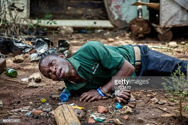 A protester seriously affected by tear gas and allegedly beaten up by police officers lays on the ground with handcuffs on after being arrested in...