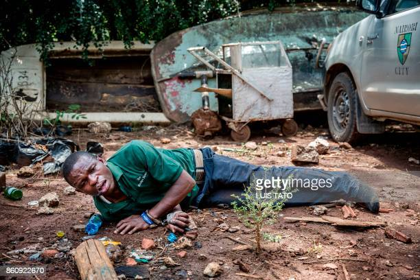 TOPSHOT A protester seriously affected by tear gas and allegedly beaten up by police officers lays on the ground with handcuffs on after being...