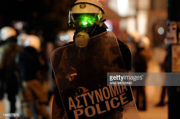 A protester shines a light from a laser beam on the face of a riot policement in front of the Greek parliament during a demonstration against new...