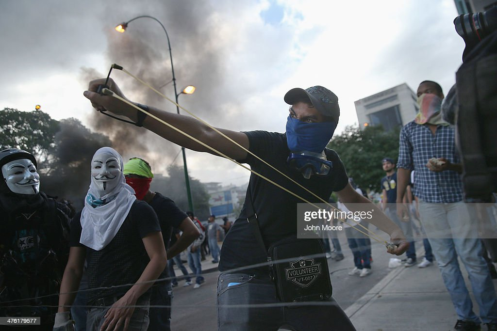 A protester shoots a slingshot at national guard troops following one of the largest anti-government demonstrations yet on March 2, 2014 in Caracas, Venezuela. Venezuela has one of the highest inflation rates in the world, and opposition supporters have protested for almost three weeks, virtually paralyzing business in much of the country.