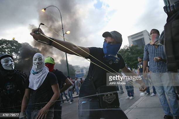 A protester shoots a slingshot at national guard troops following one of the largest antigovernment demonstrations yet on March 2 2014 in Caracas...