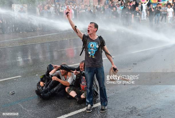 A protester shouts as riot police use water cannon trucks during the 'Welcome to Hell' rally against the G20 summit in Hamburg northern Germany on...