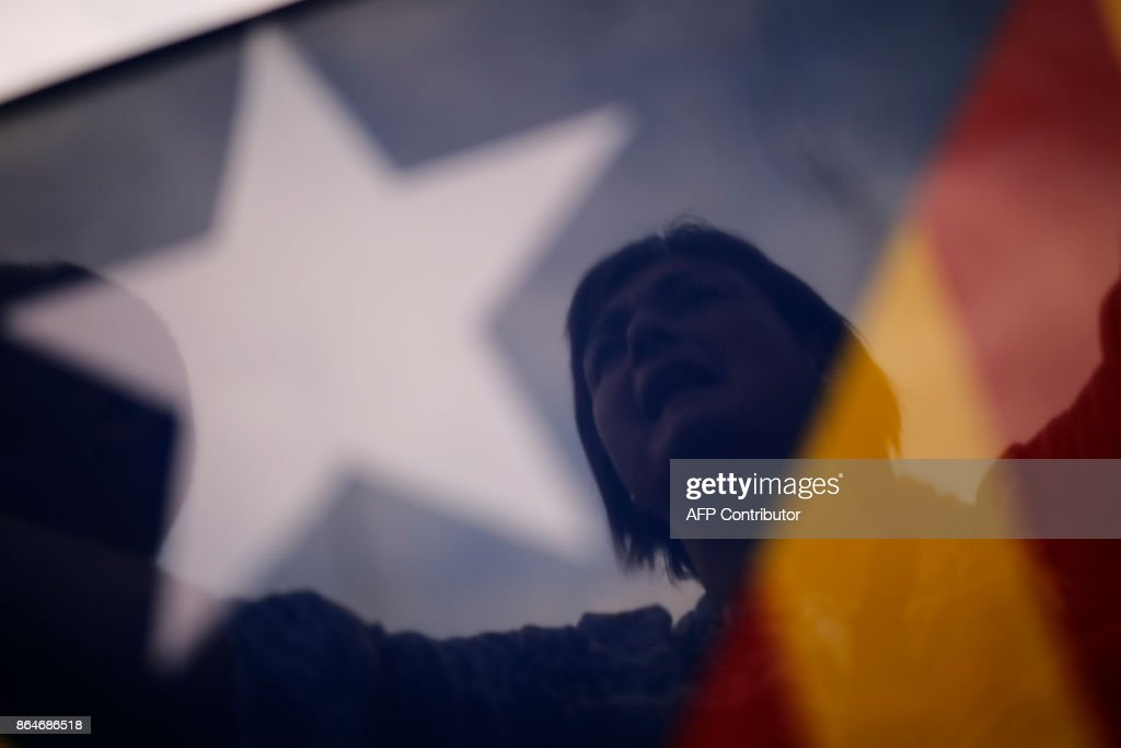 A protester shouts behind a pro-independence Catalan Estelada flag during a demonstration in Barcelona on October 21, 2017 in support of two separatist leaders Jordi Sanchez and Jordi Cuixart, who have been detained pending an investigation into sedition charges. Spain announced that it will move to dismiss Catalonia's separatist government and call fresh elections in the semi-autonomous region in a bid to stop its leaders from declaring independence. /