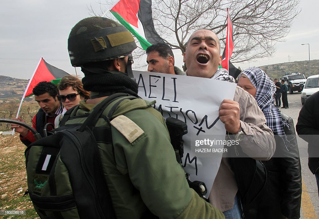 A protester shouts holding a banner in front of an Israeli soldier during a protest against planting trees by Israeli settlers in Palestinian land on the main road 60 between the West Bank cities of Bethlehem and Hebron near the Israeli settlement of Daniel on January 25, 2013. AFP PHOTO / HAZEM BADER