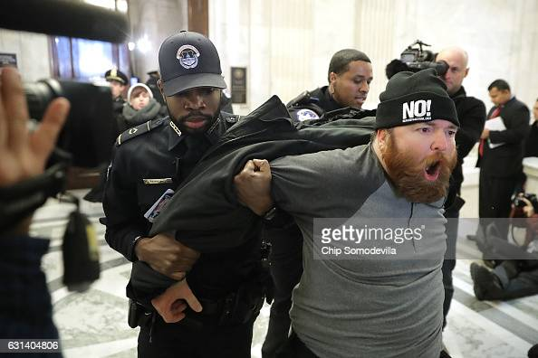 A protester shouts 'No Trump No KKK No facist USA' as he is hauled out of the Senate Judiciary Committee's confirmation hearing for Sen Jeff Sessions...
