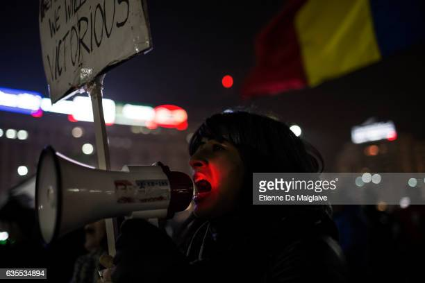 A protester shouts slogan trough a bull horn as hundreds gather in front of government headquarters at the Victory square demanding the resignation...